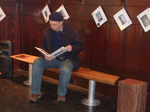 Terry Hunter reading a book of photos at Chapel Arts